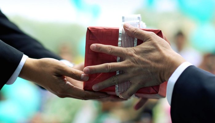 international gift etiquette. person giving a present with both hands